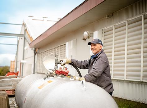 Livreur effectuant le remplissage d'un réservoir en milieu agricole