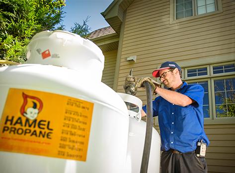Livreur effectuant le remplissage d'un réservoir en milieu résidentiel